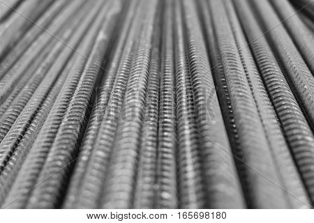 Closeup of a stack of rusty metal deformed reinforcement bars (rebar) at a building construction site. Those steel rods are used in concrete.