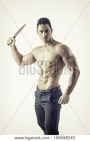 Muscular young man holding big knife ready to stab, isolated on white