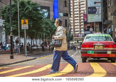 Hong Kong, China - December 6, 2016: Typical Asian senior woman with mask through the intersection in Times Square, the largest shopping mall in Causeway Bay, the luxury shopping district.