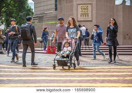 Hong Kong, China - December 6, 2016: typical asian mixed race family, crossing the Times Square intersection, largest shopping mall in Causeway Bay, the luxury shopping district.