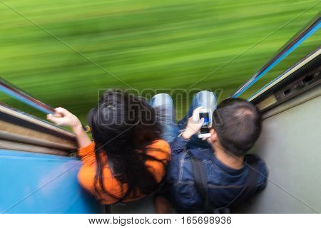 Couple traveling by train. Motion blured image creating impression of movement and speed. On the move.