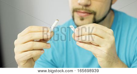 Man breaking one cigar as sign of giving up on smoking.