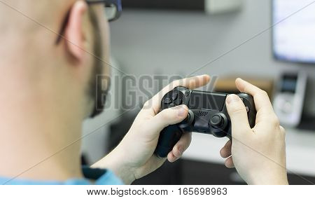 Gamer having fun with console games at home with gamepad.