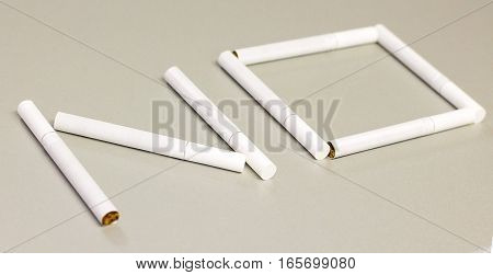 Pieces of cigarettes forming the word no - smoking prohibited.