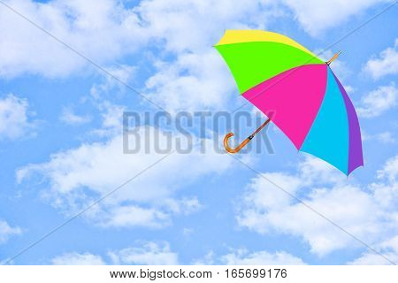 Multicolored umbrella flies in sky against of pure white clouds.Mary Poppins Umbrella.Wind of change concept.