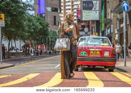 Hong Kong, China - December 6, 2016: elegant beautiful woman arab clothing with mobile in hand in Causeway bay, one of the most attractive areas for tourists and business people and good for shopping.