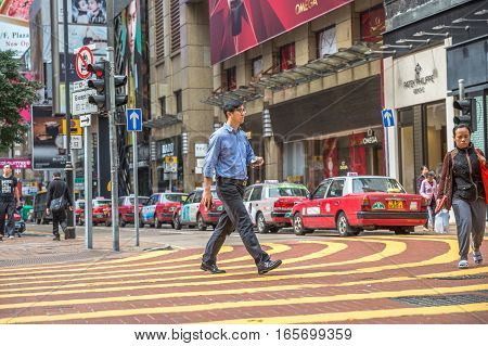 Hong Kong, China - December 6, 2016: asian elegant gentleman side walking the Times Square intersection, largest shopping mall in Causeway Bay, the luxury shopping district.