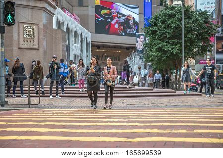Hong Kong, China - December 6, 2016: two modern asian friendly women talking along Times Square, largest shopping mall in Causeway Bay, the luxury shopping district.