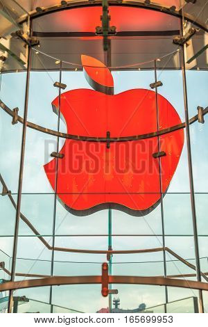Hong Kong, China - December 4, 2016: close up of Apple signboard in IFC Mall Apple store, with city sky through the glass window. Apple is world leader in consumer tablets, computers and mobiles.