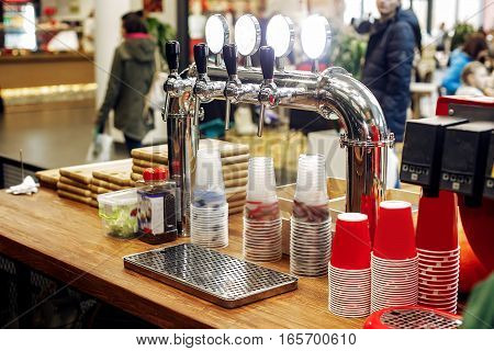Beer Bar With Stylish Taps And Plastic Cups  On Wooden Desk. Catering In Food Court At Mall Concept.