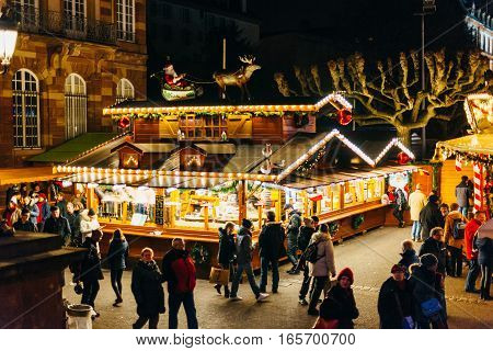 STRASBOURG FRANCE - DEC 20 2016: Elevated view of Christmas Maerket with people shoppign traditional gifts buying holiday food during oldest Christmas market in the world