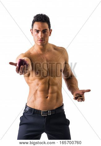 Muscular shirtless young man deciding between healthy fruit and unhealthy cookies, isolated