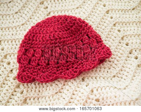 Red crocheted baby hat in a variety of stitches and with scalloped edging