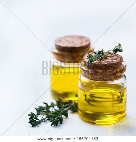 Health and beauty, still life concept. Organic essential thyme oil in a small glass jar with green leaves on a white rustic wooden table
