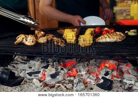 Vegetables And Meat Grilling. Hand With Tongs And Mushrooms Corn Pepper Tomatos Garlic On Grill. Cat