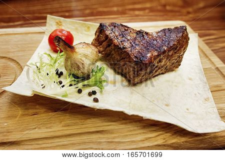 Juicy Meat Grilled Steak With Red Pepper Tomato And Garlic. Serving Beefsteak On Wooden Desk. Cateri