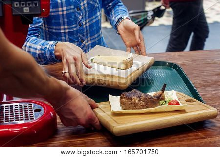 Serving Juicy Grilled Steak With Fried Vegetables And Cheesecake To Customer Or Waiter On Wooden Des