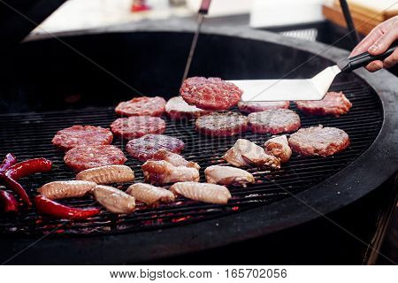 Pork Meat And Chicken Cutlets With Pepper Grilling For Burgers. Chef Working With Spatula. Catering