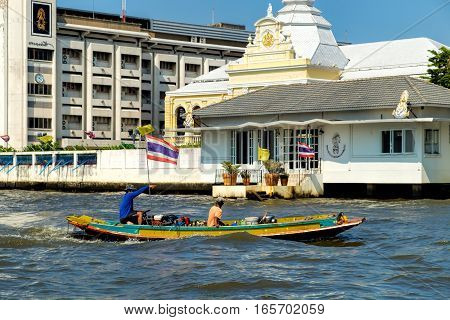 Bangkok, Thailand - December 22, 2015: Two men floating down the Chao Phraya river in small boat with Thai flag looking at interesting sights ahead.