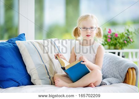 Adorable Little Girl Wearing Eyeglasses Reading A Book In White Living Room