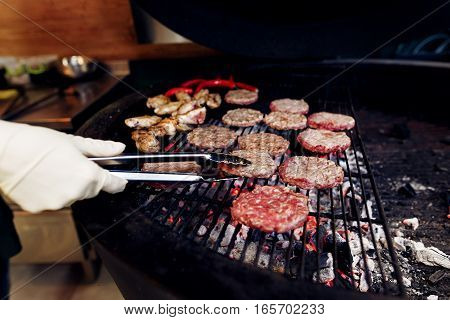 Pork Meat And Chicken Cutlets With Pepper Grilling For Burgers. Chef Working With Tongs In Gloves. C