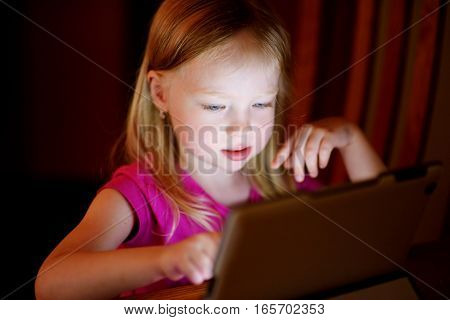 Adorable Girl Playing With A Digital Tablet In A Dark Room