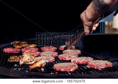 Pork Meat And Chicken Cutlets With Pepper Grilling For Burgers. Chef Working With Tongs. Catering In