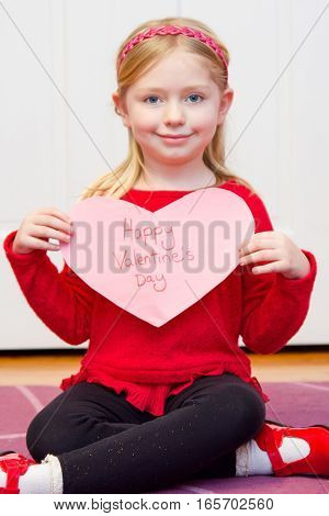 adorable school age girl holding sign for valentine's day