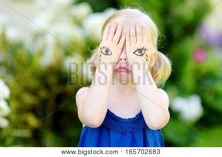 Cute Little Girl Covering Her Face With Her Hands On Summer Day