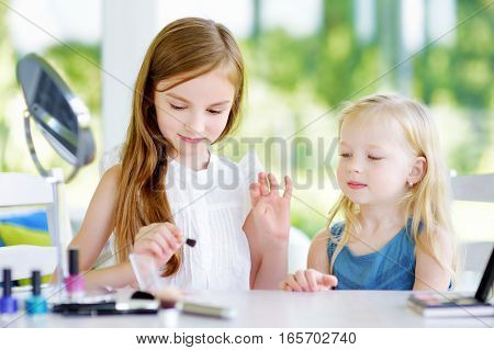 Two Cute Funny Sisters Applying Make-up On Sunny Summer Day At Home