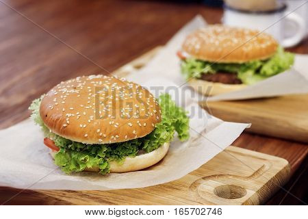 Yummy Burger. Serving Cheeseburger Or Hamburger With Salad Tomatoes Onion  On Wooden Desk. Catering