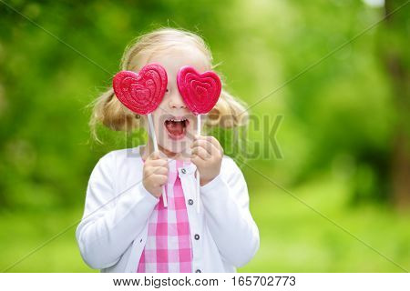 Cute Little Girl Eating Huge Heart-shaped Lollipop Outdoors On Beautiful Summer Day
