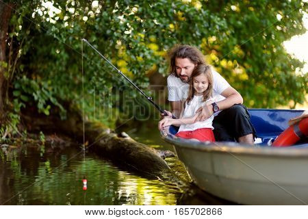 Cute little girl and her father having good time together in a boat by a river at beautiful summer evening. Child and her parent fishing.