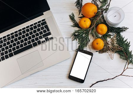 Stylish Laptop And Phone With Empty Screen On White Wooden Background With Christmas Oranges And Gol