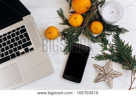 Stylish Christmas Flat Lay. Laptop And Phone With Empty Screen On White Wooden Background With Seaso