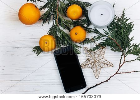 Stylish Phone With Empty Screen And Christmas Oranges And Golden Star On White Rustic Wooden Backgro