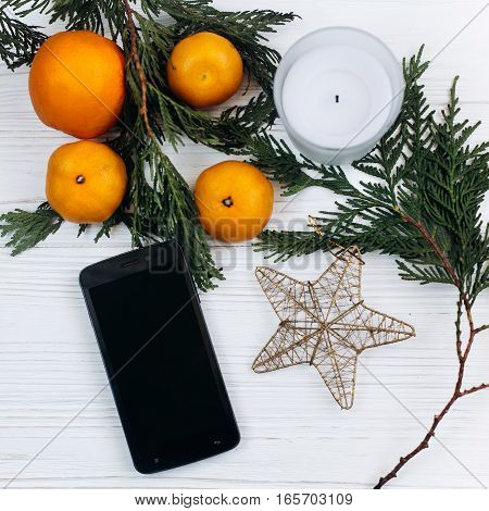 Stylish Christmas Flat Lay. Phone With Empty Screen And Oranges And Golden Star On White Rustic Wood