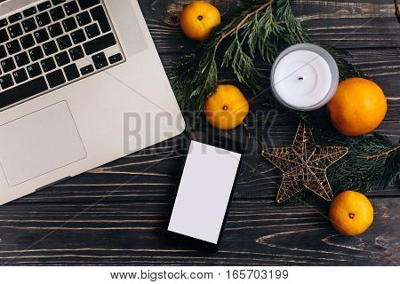 Christmas Flat Lay Of Laptop And Phone With Empty Screen And Branches And Oranges And Star On Black