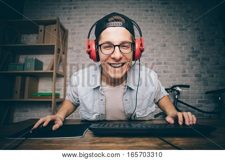 Young man playing game at home and streaming playthrough or walkthrough video. Smiling guy is happy to try this new kind of entertainment. He is looking at the camera