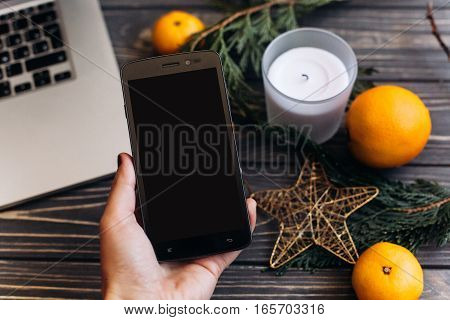 Hand Holding Phone With Empty Screen For Christmas Seasonal Advertising On Background Of Green Branc
