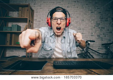 Young man in red headphones playing game at home and streaming playthrough or walkthrough video. Crazy guy is shouting because of unjustice in virtual game and pointing at the screen with one finger