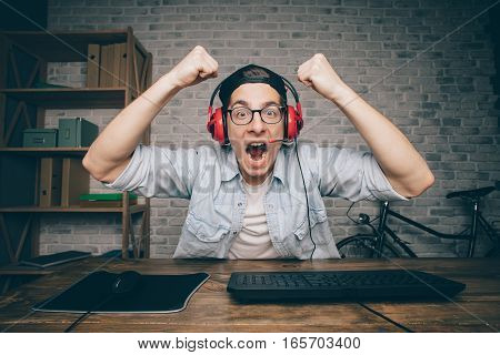 Young man playing game at home and streaming playthrough or walkthrough video. Attractive man is wearing eyeglasses and earphones. He is happy to win this fight in vr. Boy lifting his fists above the head