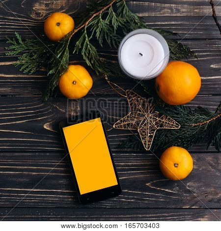 Phone With Empty Screen On Christmas Background Of Green Branches And Oranges And Golden Star On Bla
