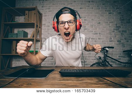 Young man playing game at home and streaming playthrough or walkthrough video. Shouting crazy guy has won his last and the hardest battle in vr. He is looking at camera with aggressively happy face expression shaking with one fist in front of it.