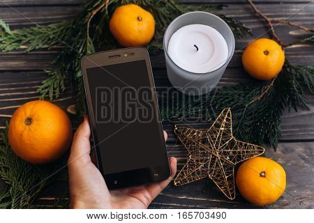 Hand Holding Phone With Empty Screen On Christmas Background Of Green Branches And Oranges And Golde