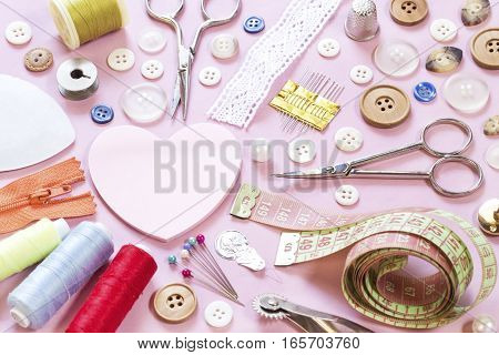 Various sewing items on pink paper background