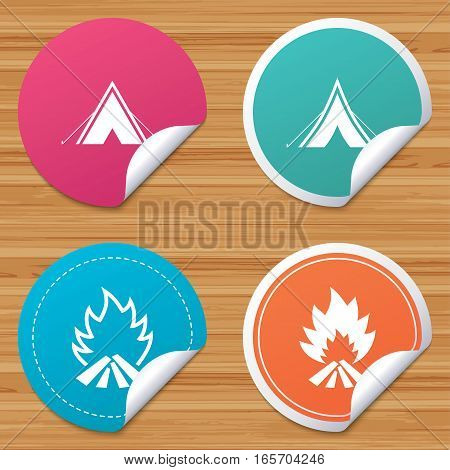 Round stickers or website banners. Tourist camping tent icons. Fire flame sign symbols. Circle badges with bended corner. Vector