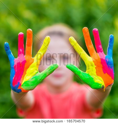 Little girl with hands painted in colorful paints ready for hand prints - very shallow depth of field - only hands are sharp