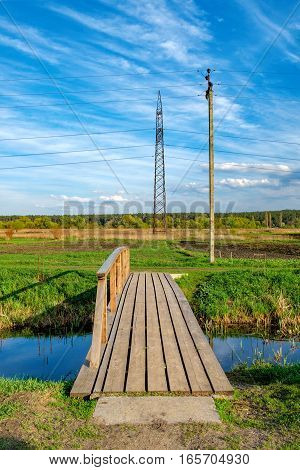 Rural landscape with road to small river green meadow and forest on the horizon in spring, Irpin, Ukraine. Banks of a small river with wooden bridge over it.