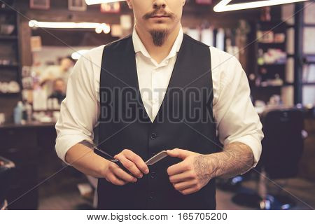 Cropped image of bearded hairdresser in stylish classic wear holding a straight razor while standing at the barbershop